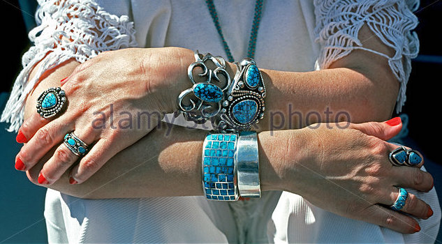 a-woman-displays-her-pawn-jewelry-collection-of-turquoise-rings-and-e4gbkk